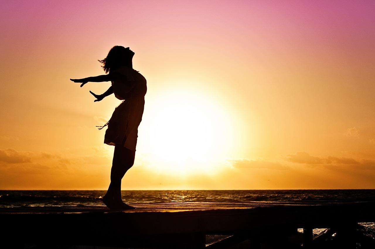 afvallen met yoga. dame die flink inademt bij zonsondergang.